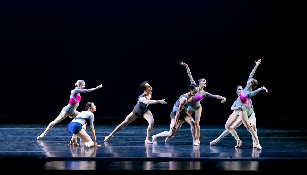 A group of six men and women in color-block leotards and short bodysuits gesture toward a woman at far stage left.