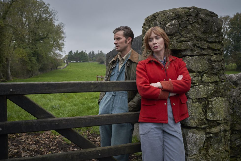 amie Dornan (Left) stands beside Emily Blunt (Right) with a wooden gate separating the two. Both face the camera, but look past it at the Irish, green landscape. The sky is dreary and grey. He wears farming overalls and a collared brown shirt with a large jacket. She wears a red jacket and similar farm overalls.