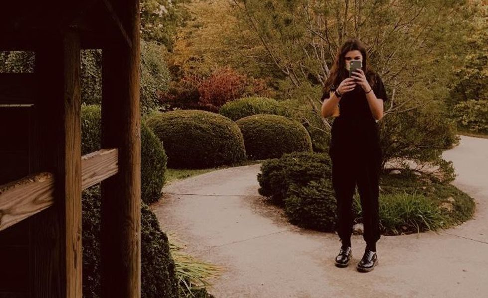 Fashionable girl standing in garden taking a picture of the person behind the camera.