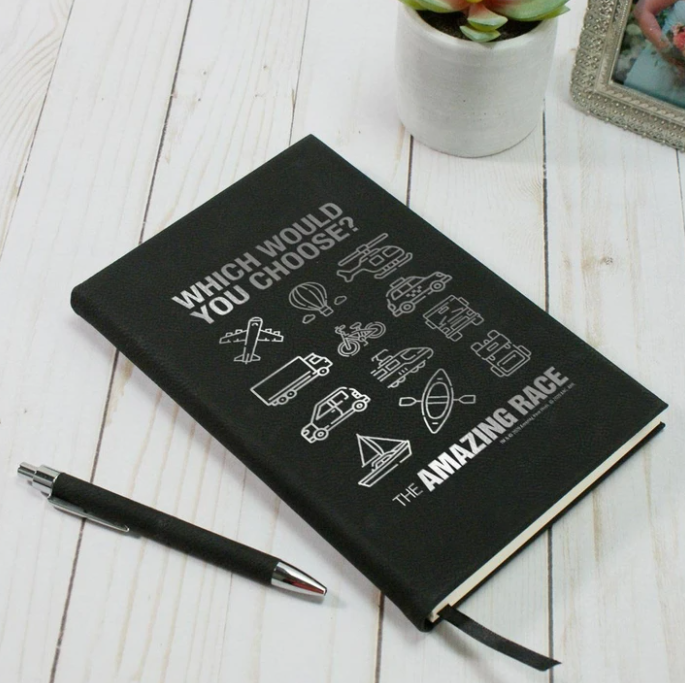 Black faux leather journal with The Amazing Race logo and transportation icons