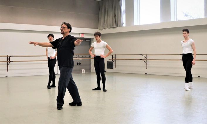 Dhouloukhadze, a man with a goatee and black shirt and pants, demonstrates a fourth position prep while three teenage boys look on in a ballet studio.