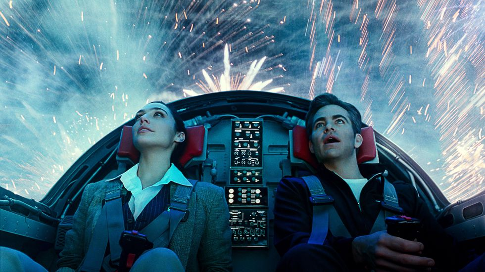 Gal Gadot as Diana Prince (left) and Chris Pine as Steve Trevor (right) take a ride in an airplane on Fourth of July. The photo is of the couple angled upwards so viewers can see fireworks light up the sky above them as they sit in the cockpit.