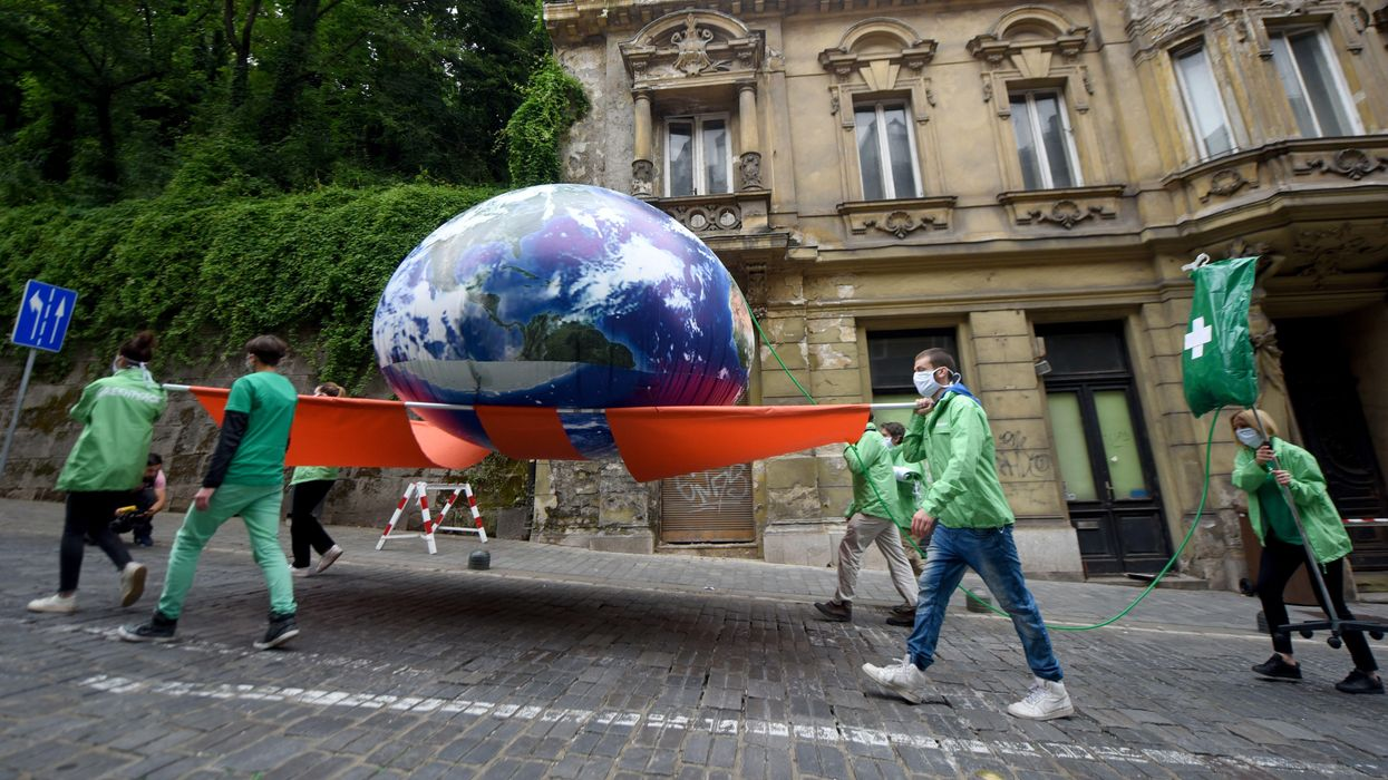 Greenpeace activists carry on a stretcher a giant balloon representing planet Earth.