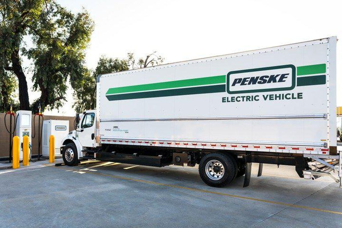 Penske Electric Vehicle in front of charging station