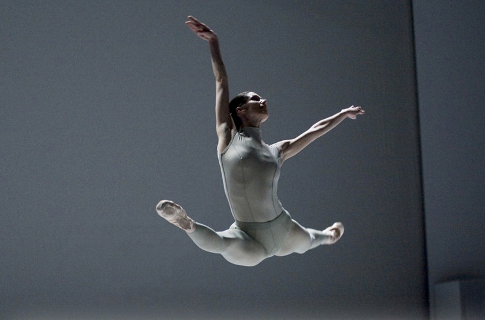 Wearing a grey unitard and against a grey set, Juleen leaps in an expansive grande jete, one arm extended above her and the other to the side