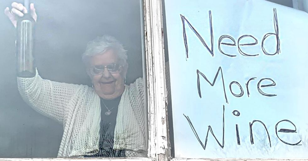 82-Year-Old Woman in Quarantine Holds 'Need More Wine' Sign at Her Window