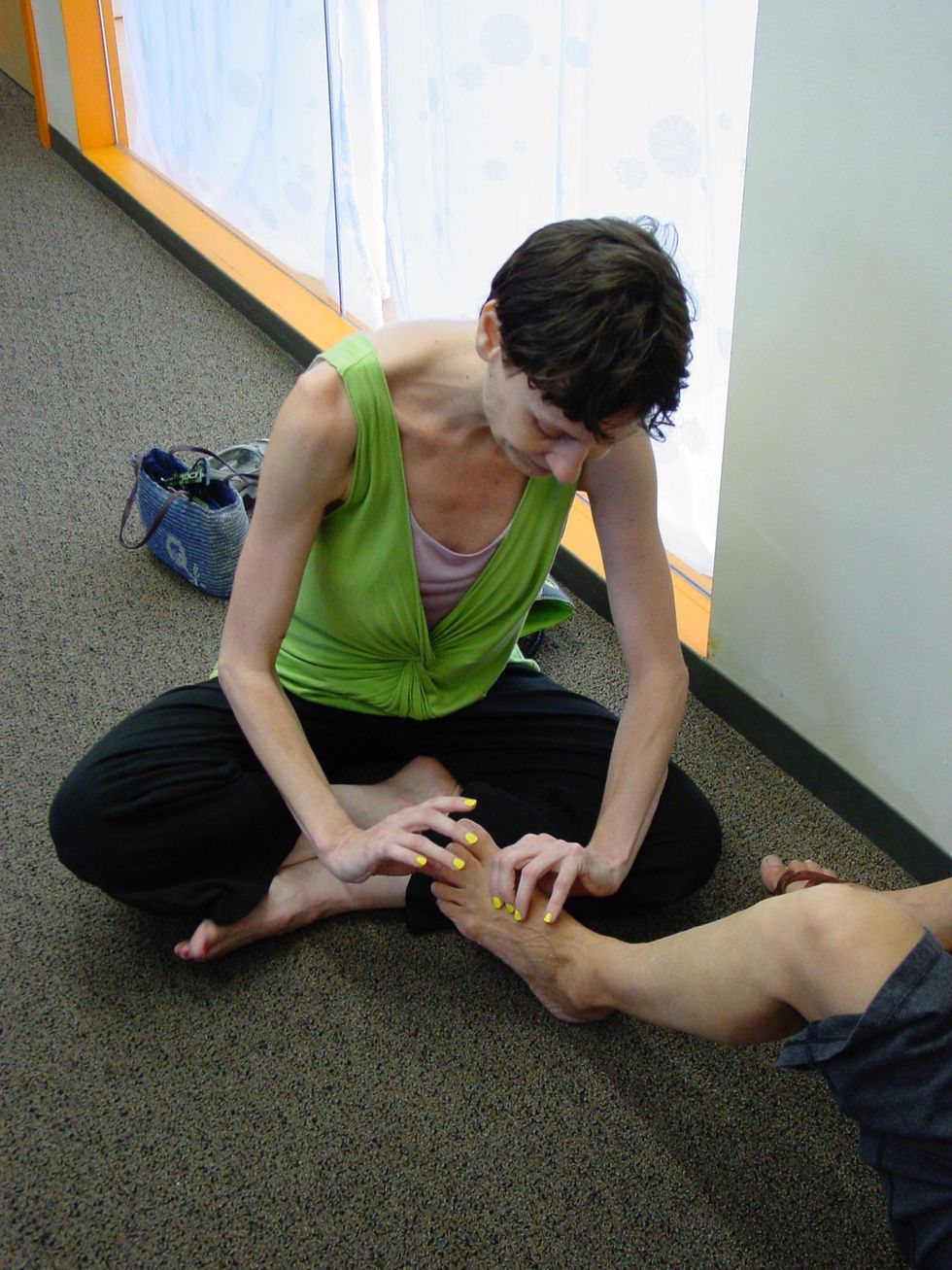 Accardi, wearing black pants and a bright green shirt, sits crosslegged on the floor, with another person's foot in her lap, which she holds gently