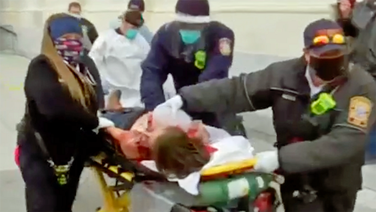 WATCH: Paramedics bring bloody woman out of capitol on a stretcher