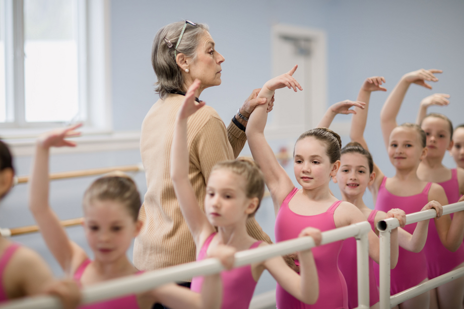 Bennett, wearing a tan sweater, adjust a young student's fifth position at the barre, looking stern. A row of girls, all in pink leotards, are in the same position, tightly packed at the barre.
