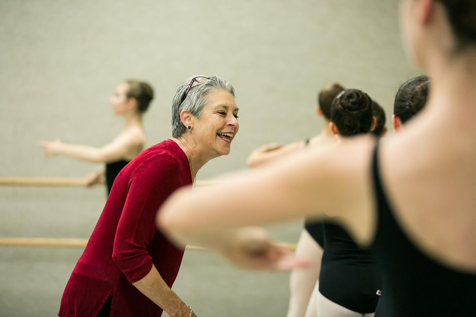 Bennett, with short grey hair, glasses on her head and a velvet red shirt, smiles and leans down towards a teenage girl at the barre, whose back is to the camera