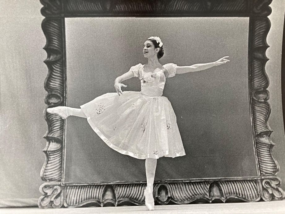 A black and white shot of a young Bennett performing in a floral headband, long romantic tutu and pointe shoes, with a setpiece behind her that looks like a large picture frame