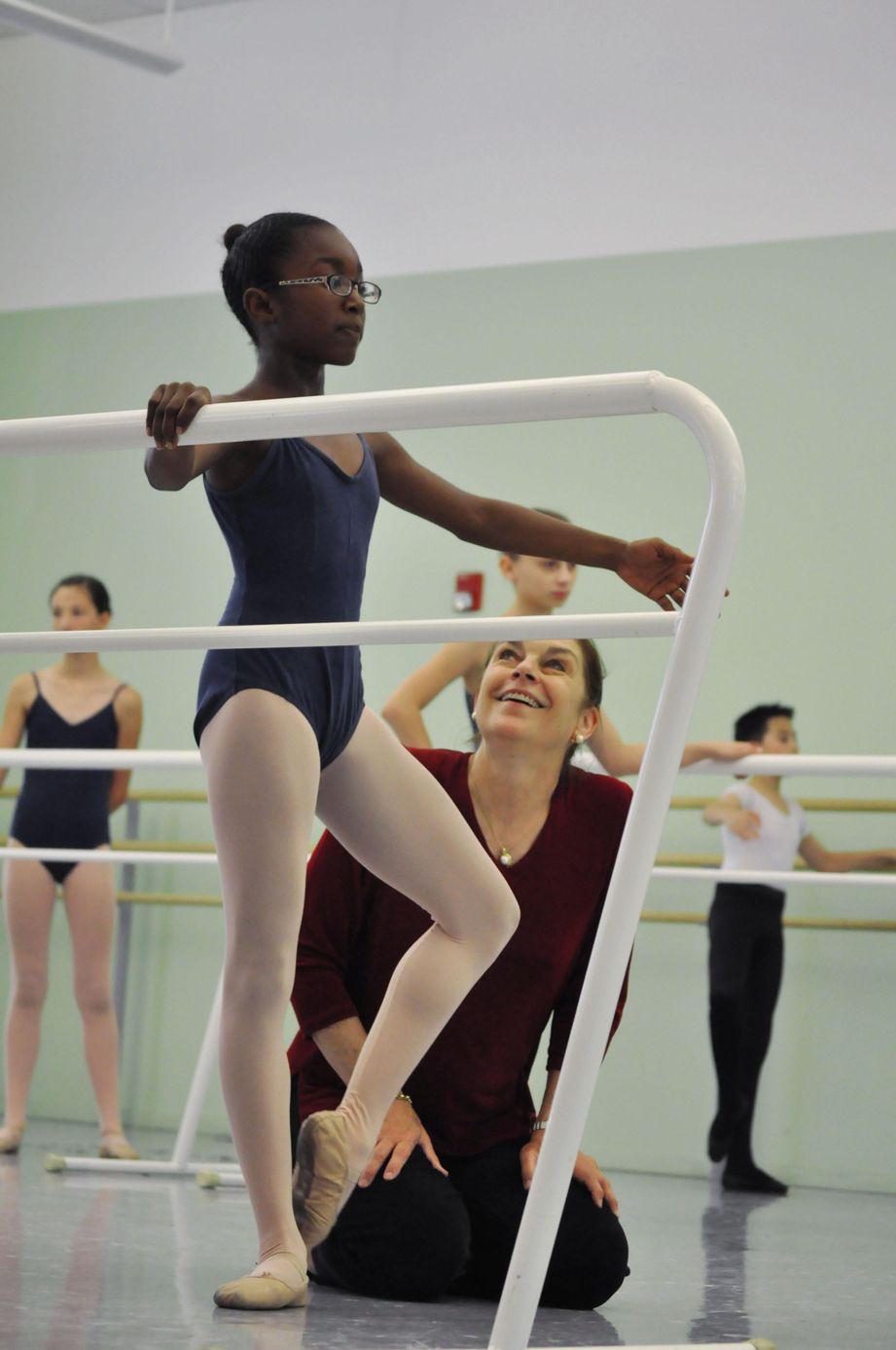 Bennett kneels beside a young student who is in coupe at the barre, smiling up at her