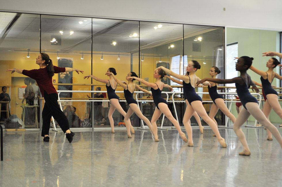 Bennett, in a red shirt and black pants and with her brown hair in a ponytail, leads a class on pre-teen ballet students
