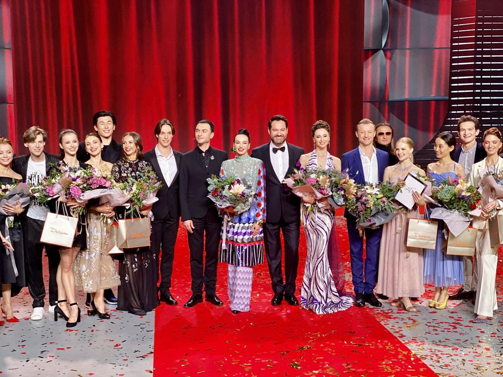 A staggered line of 17 men and women in dress clothes stand and smile for the camera in front of a red curtain.             </div></div><p style=