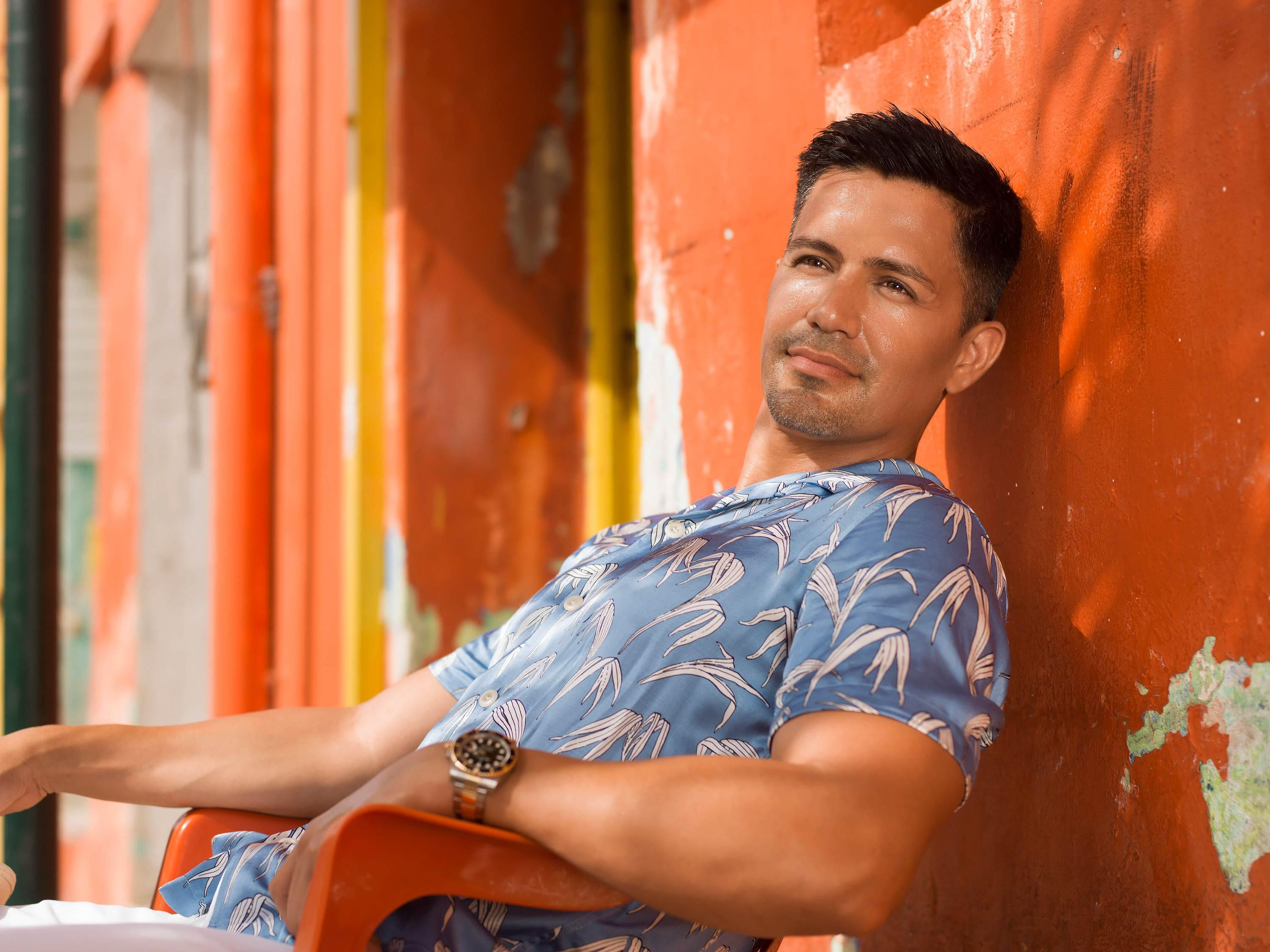 Jay Hernandez reclining in an orange chair against a bright orange wall on a street in Cancun