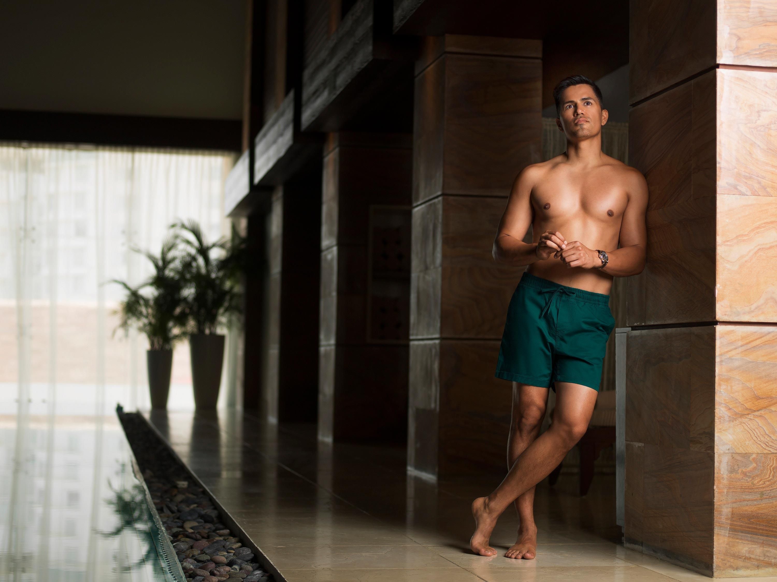 Jay Hernandez poses in green swim trunks at a Cancun resort