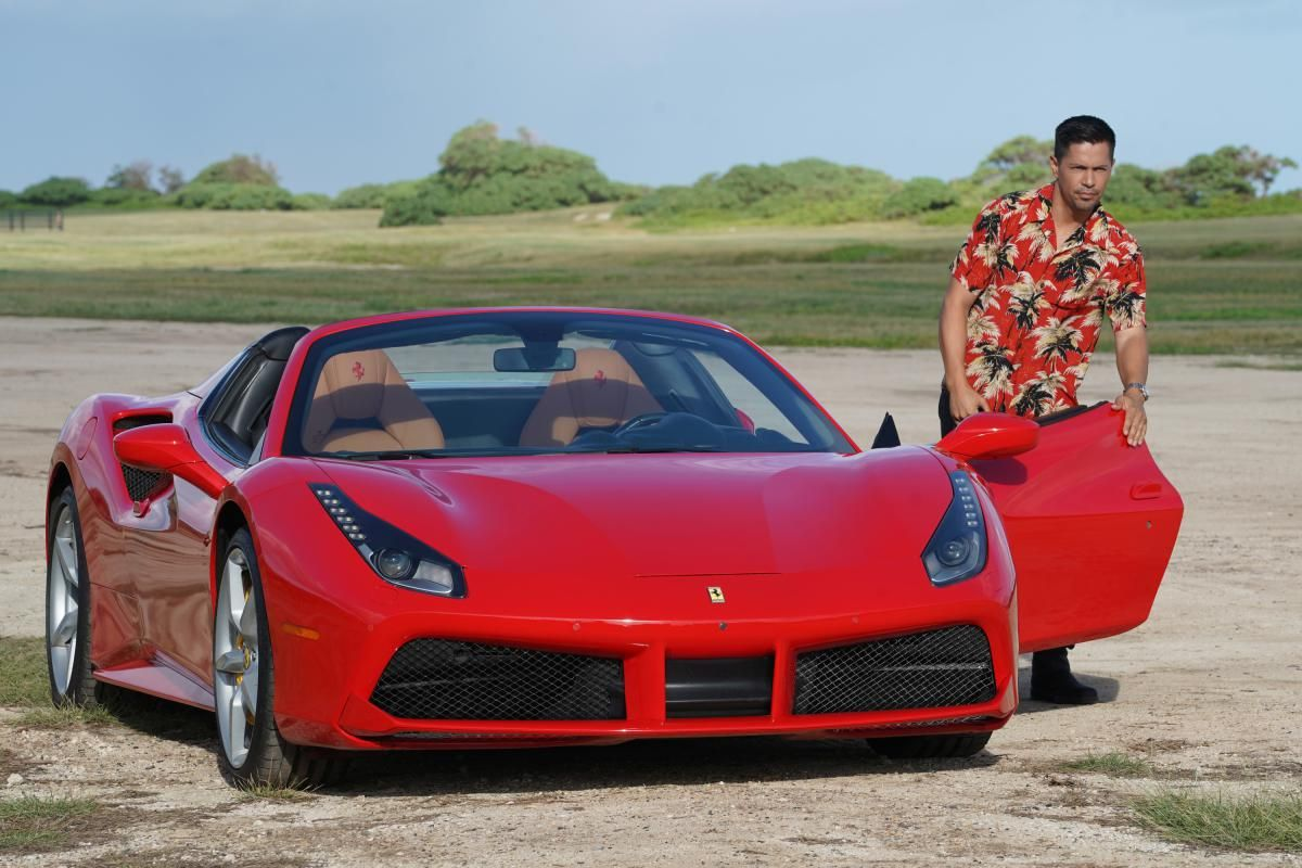 Magnum getting out of his red Ferrari wearing a red Hawaiian shirt