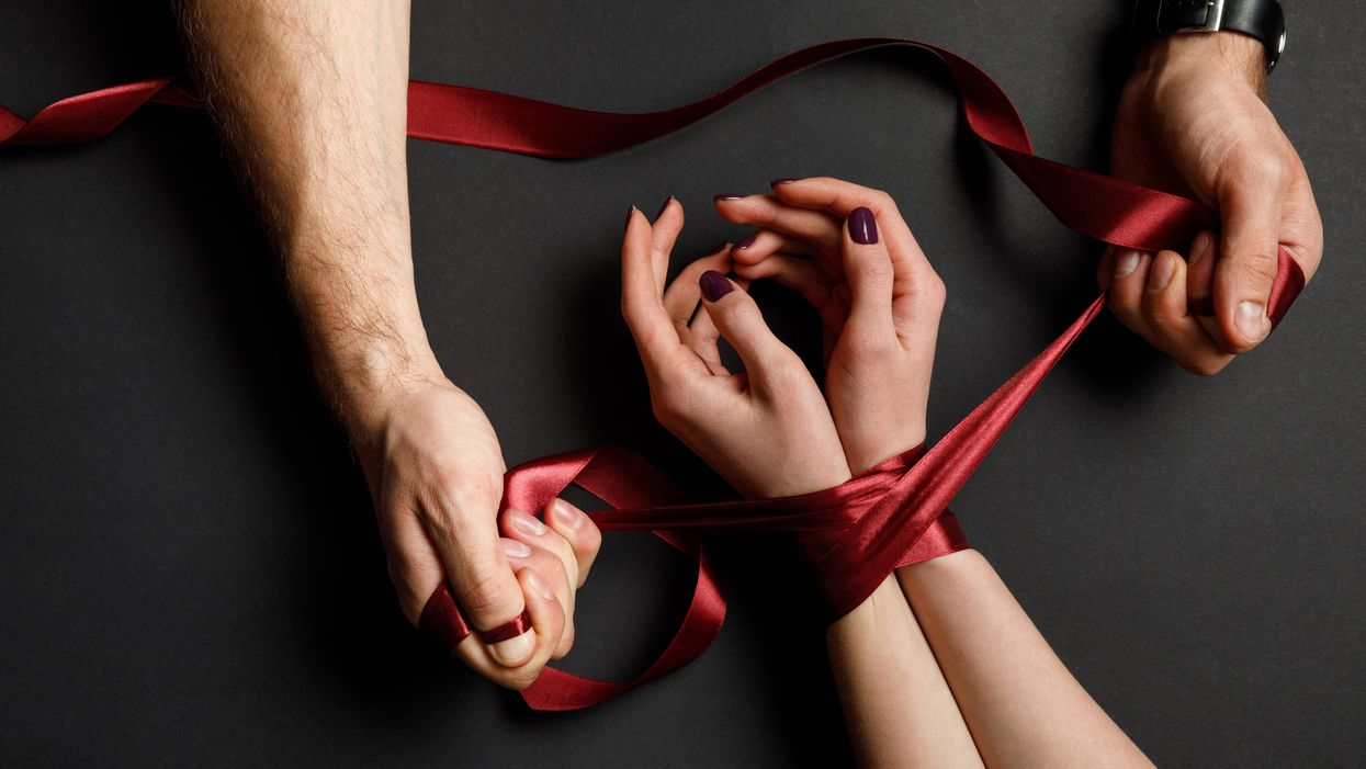 woman's hands bound with ribbon BDSM