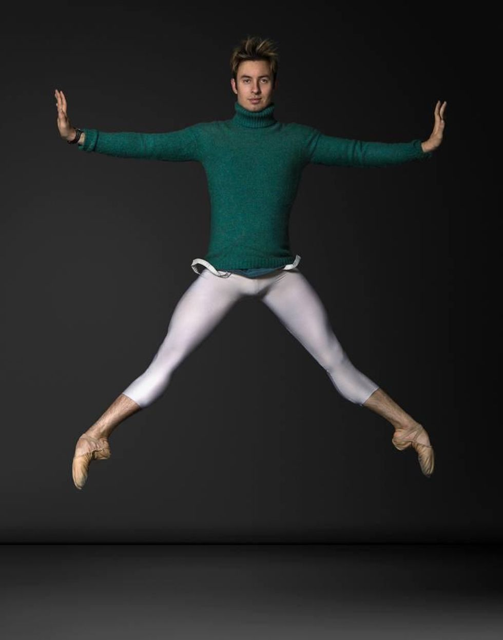 A white male dancer in a green turtleneck sweater, calf-length white tights and tan ballet slippers jumps in second position with his arms out to the side and hands flexed.