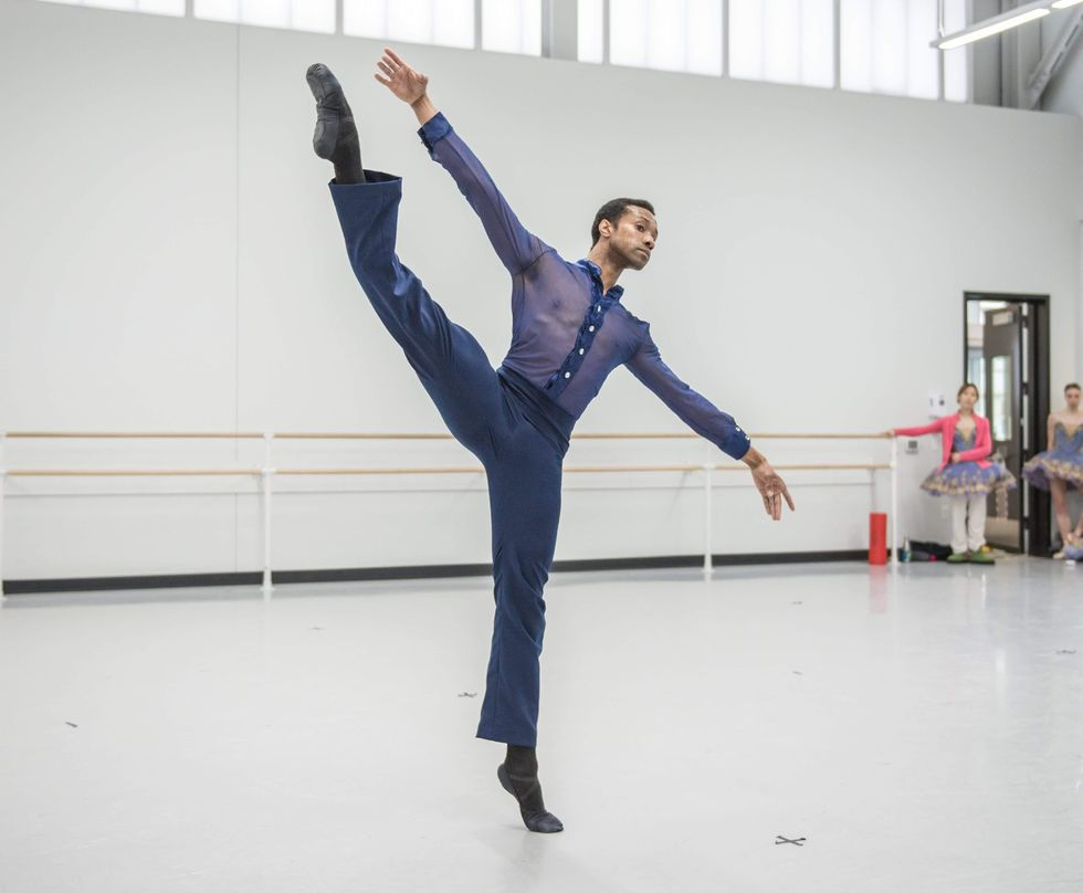 An African American male dancer, wearing indigo pants and a mesh, indigo button-down blouse, does a grand battement with his right leg and lean off balance to the left, with his arms out and tilted in a diagonal.