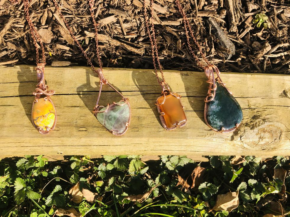 Four copper-wire necklaces with a yellow, light green, orange and dark green stone, respectively, are lined up right to left on a plank of wood.