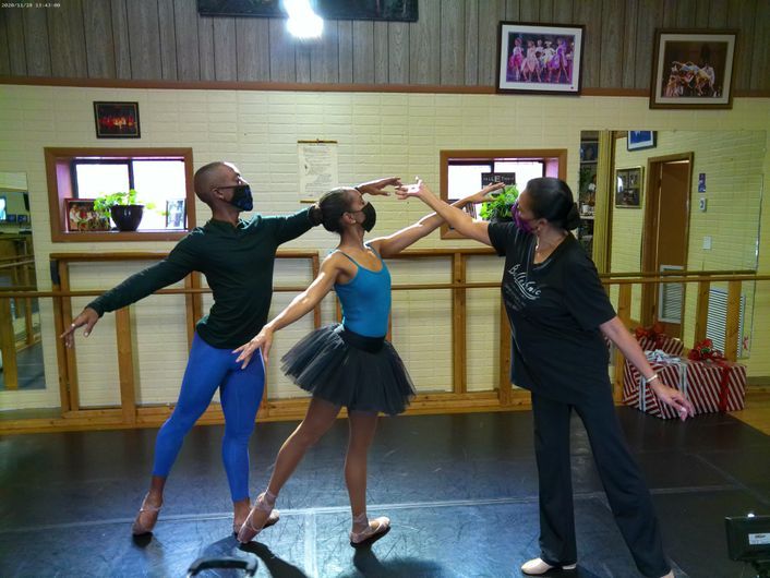 Two dancers in blue and black practice clothes and face masks, the woman in pointe shoes, pose together in a first arabesque tendu. Abarca Mitchell steps out of a mirrored pose as she adjusts the fingertips of the male dancer.