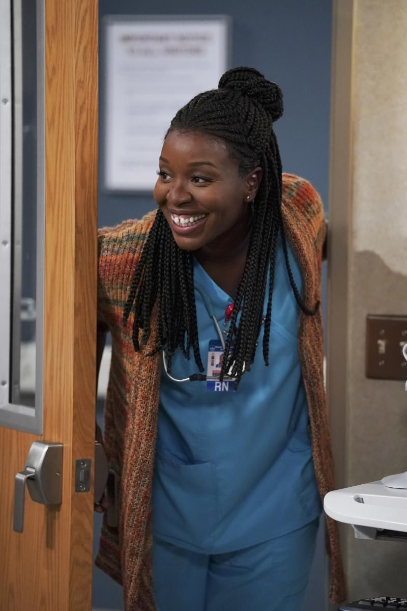 Abishola smiling as she enters a hospital room