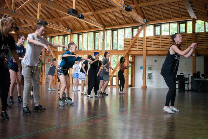 Michelle Dorrance, wearing silver tap shoes, black leggings and shirt and large hoop earrings, teaches a tap class of dozens of teenagers in a light-filled barn studio