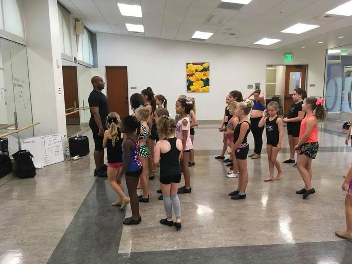 A group of elementary school aged- girls stands in around a dance studio. A teacher, a young black man, stands in front of the studio, talking to them