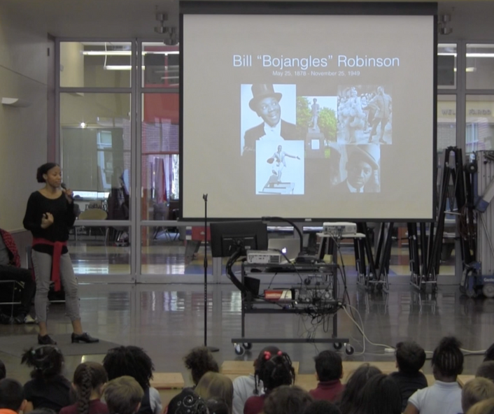 "Griffith stands next to a large screen with a powerpoint presentation showing the name ""Bill Bojangles Robinson"" with some photos. She holds a microphone and speaks to a large group of students who sit on the ground"