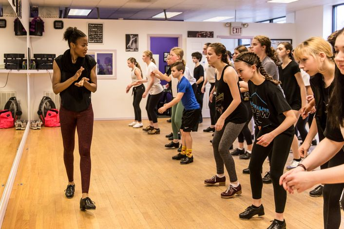 Griffith walks across the front of a studio, clapping her hands, as a large class of teen students practice a tap combination