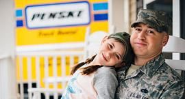 Soldier with daughter and a Penske truck in background