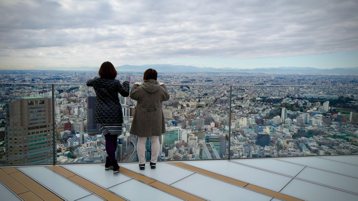 Two women looking over a city from a viewing platform illustrating the concept of self-indifference.