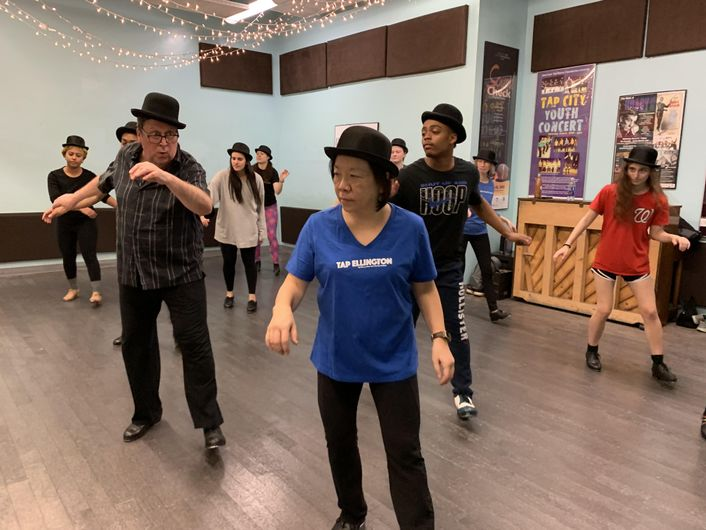 Tony Waag, a middle-aged white man, leads a small studio of adult tap dancers, who all wear top hats.