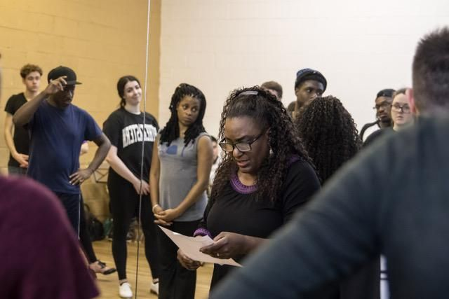 Deborah Mitchell, a middle-aged Black woman, leans on the mirror of a dance studio, looking down at a piece of paper in her hands. Several adult dancers surround her, listening.