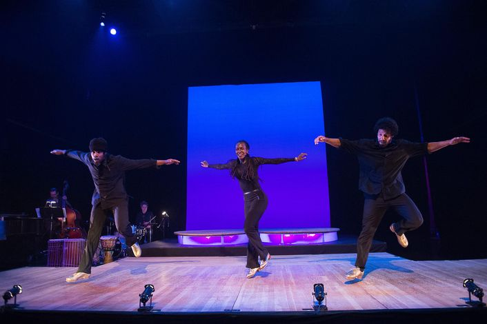 Jason Samuels Smith, Dormeshia and Derick K. Grant dance on a small stage, with a band in the corner. They wear all black, with shiny tap shoes, and jump slightly in the air with their arms to the sides.
