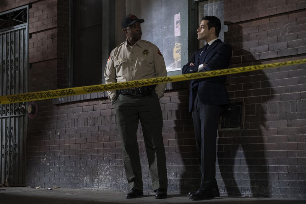 """Denzel Washington (left) and Rami Malek (right) stand behind a caution tape line against a brick wall in John Lee Hancock's crime thriller """"The Little Things."""" The ambiance of the photo is dark, bleak and mysterious due to low lighting and exposure."""