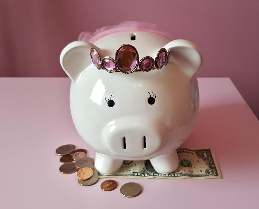 A cute white ceramic piggy bank wears a jeweled tiara and pink tutu, and stands on top of a dollar bill and next to a pile of coins.