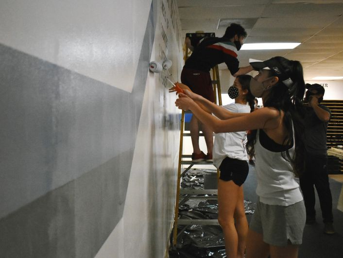 Two women with long brown hair and wearing masks, T-shirts and shorts use rollers to paint a wall with white paint. Behind then a young man in black shorts and a multi-colored shirt stands on a ladder.