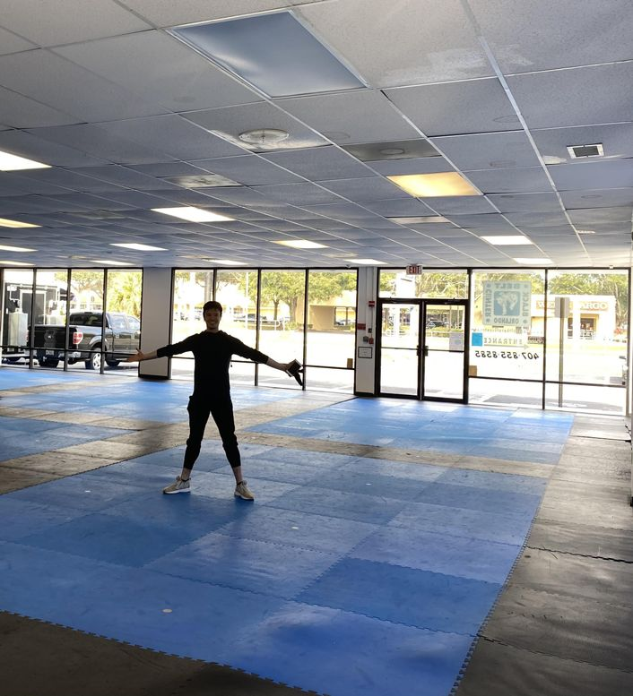 Inside a large, low-ceilinged but sunny studio space, Joseph Gatti spreads his arms and legs wide and smiles happily. The walls are covered in floor-to-ceiling windows and the black floor includes large squares of blue.