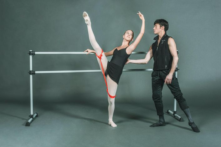 A young white baller student in black leotard and skirt and pink tights and slippers performs d\u00e9vellop\u00e9 devant with her inside leg while holding onto a portable barre with her right hand. A red resistance band is tied around each thigh. Joseph Gatti, wearing black practice clothes and ballet shoes, stands behind her and touches the small of her back to help her balance.