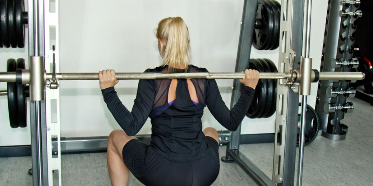 Rear view of a young adult girl doing heavy squats in the gym with a barbell.