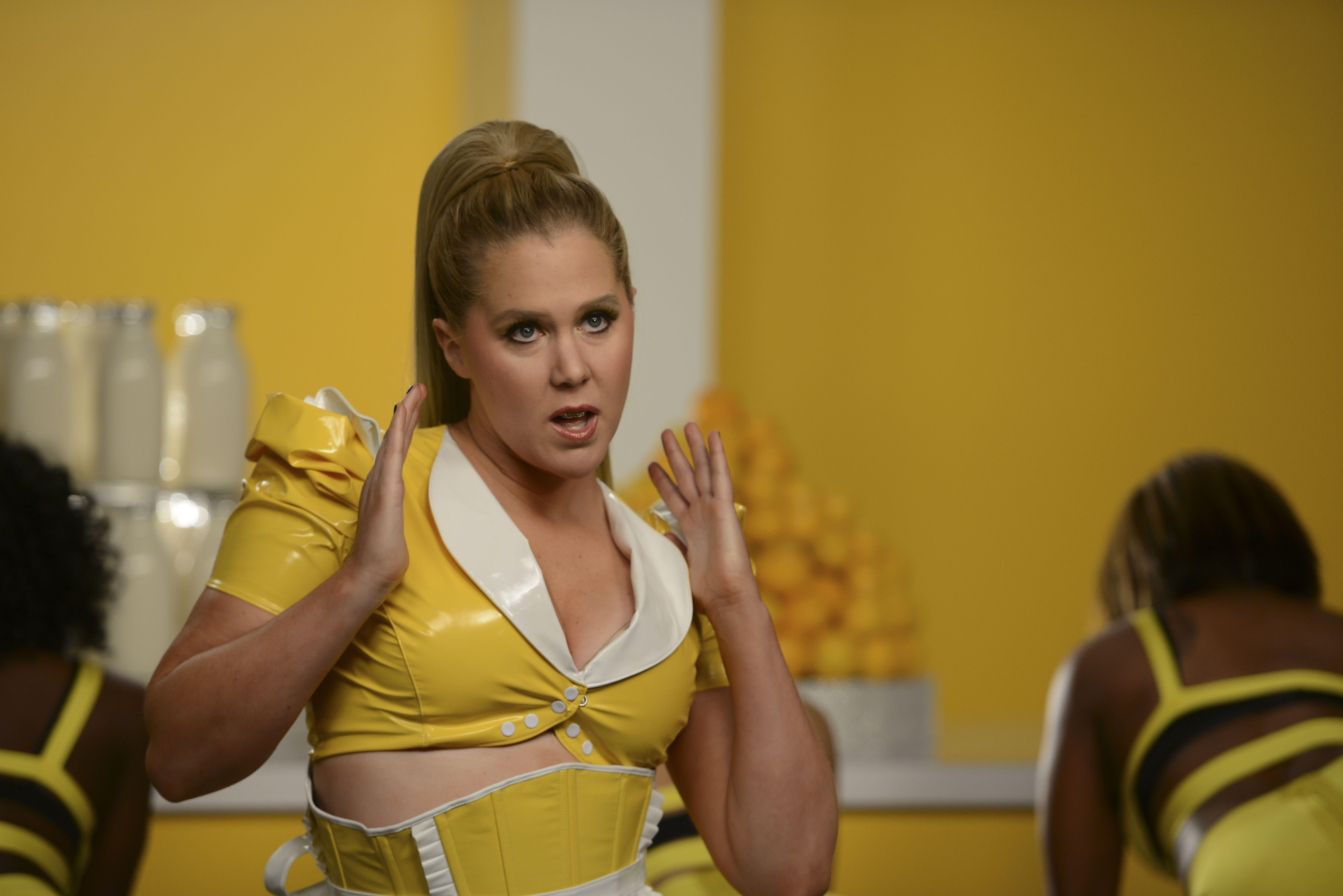 Amy Schumer dressed in yellow in a music video