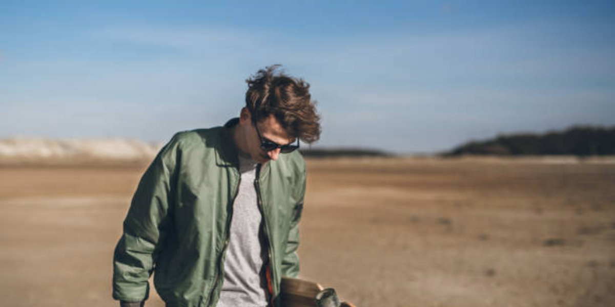 Young man wearing bomber jacket on beach