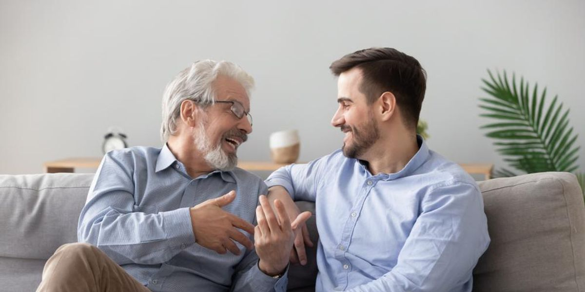 Mature man and young man talk on couch