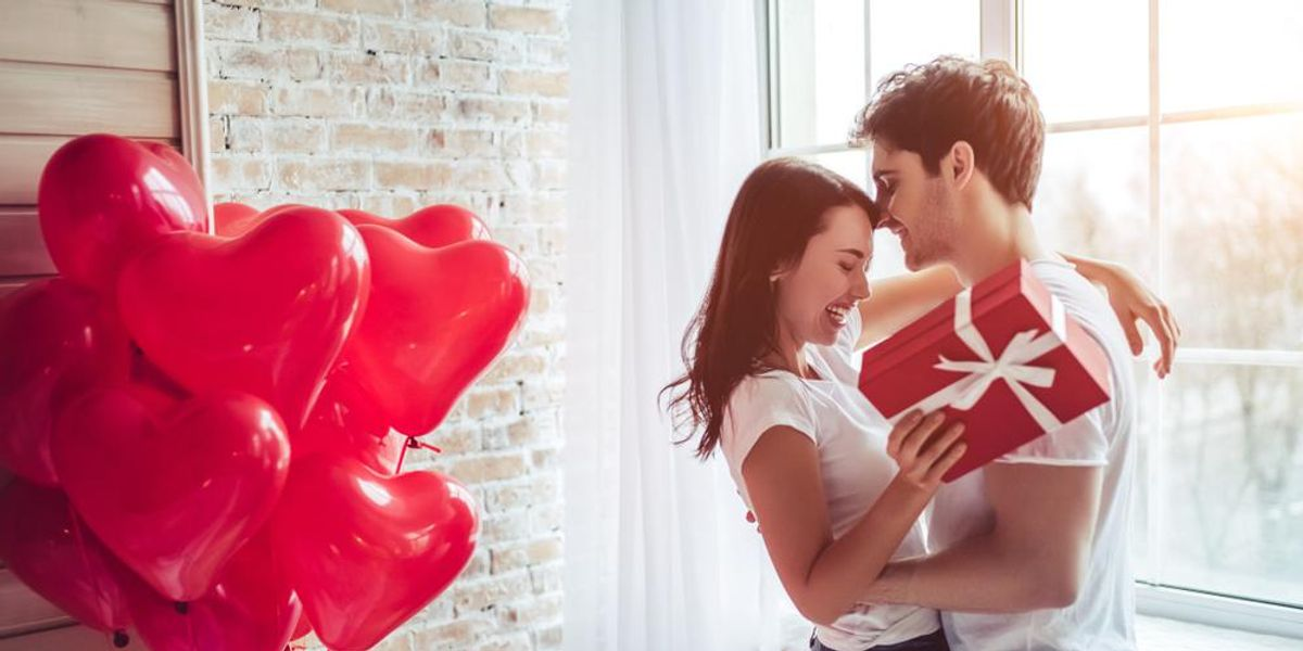 A man and woman hug each other. She is holding a red box with white ribbon. They're next to a bouquet of heart balloons.