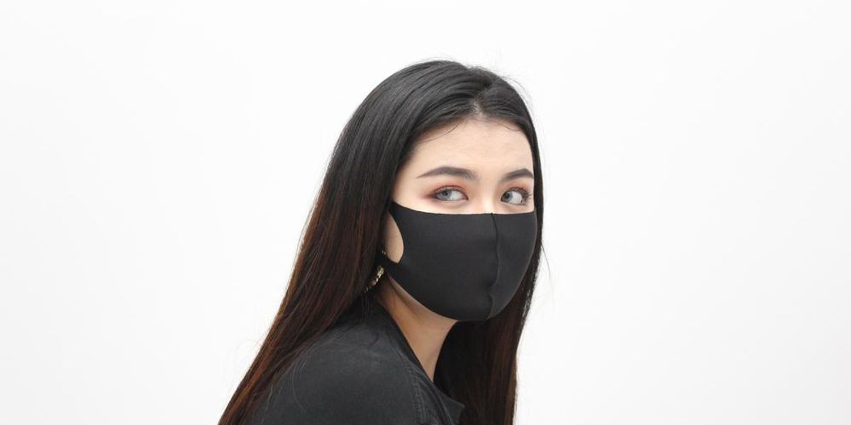 A woman wearing a black mask looks off camera