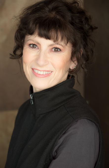 Dr. Paula Thomas is a middle-aged white woman wearing a long-sleeved grey shirt and a black vest. Her dark, curly hair is in an updo, and falls around her face. She has a bright smile