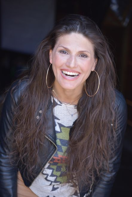 Leslie Scott Zanovitch is a young white woman, wearing a graphic shirt, a leather jacket and large hoop earrings. She has long wavy brown hair that spills down her shoulders, and she has a big, open smile