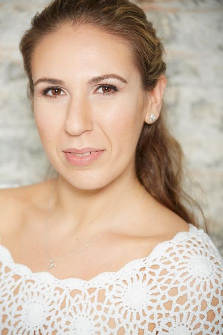 Emily Buffered, a young white woman, wears a lacey white sweater, and silver earrings and a necklace. Her light brown hair is back in a ponytail, and she smiles softly at the camera